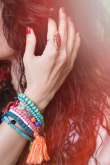 woman hand in hair with boho style jewelry, beads bracelets and ring closeup outdoor summer