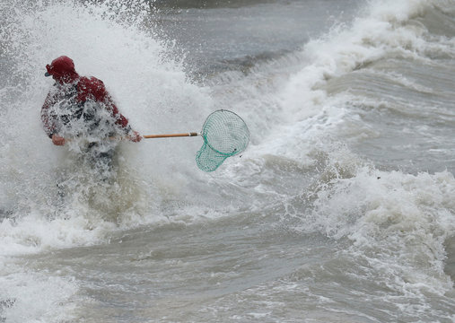 A man using a net to try to catch fish which escaped from an offshore fish farm gets splashed by a wave as gale force winds and rough seas lash the Maltese islands, in St Paul's Bay