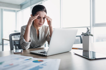 Young attractive woman at modern office desk. She has severe headache. Office syndrome concept