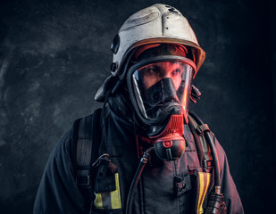 Close-up portrait of a firefighter in safety helmet and oxygen mask. Studio photo against a dark textured wall