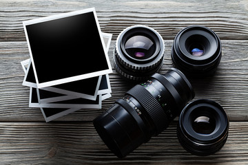 Lenses and photo frames on wooden table