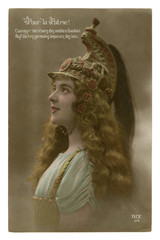 French historical colored photo postcard: A beautiful young girl with long wavy hair in a patterned cavalry helmet with plumage. world war one 1914-1918. Republic of france