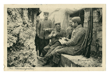 German historical photo postcard:  Soldiers in the trench Smoking pipes, playing cards. one holds a frying pan with food. In between attacks. world war one 1914-1918. Germany