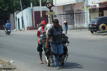 A man pulls a cart with suitcases as he walks towards the border between Venezuela and Colombia, a day after clashes between opposition supporters and Venezuela's security forces, in San Antonio del Tachira