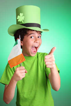 Happy kid wearing a green Leprechaun's hat and holding an Irish flag