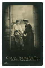 Old German postcard: Photo: couple in love: sailor and girl on the balcony on the background of a warship at sea. romantic date. world war I 1914-1918, Germany