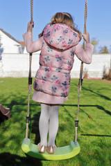 fillette sur balançoire avec anorak rose de dos