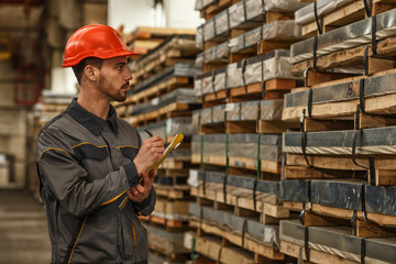 Shot of a young bearded warehouse worker wearing protective hardhat and uniform making notes on his clipboard while checking stock supplies. Export, import, heavy industry retail concept Wall mural