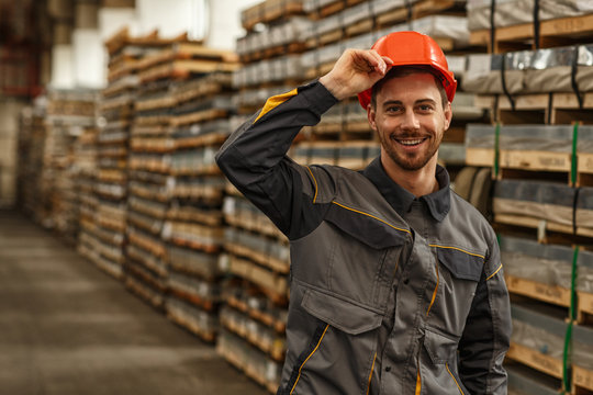 Cheerful handsome male engineer smiling to the camera while putting on protective hardhat, posing at the storage of metalworking factory. Employment, industry, safety concept