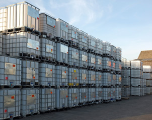 used metal framed intermediate bulk containers stacked on pallets waiting to be cleaned or recycled in an industrial yard