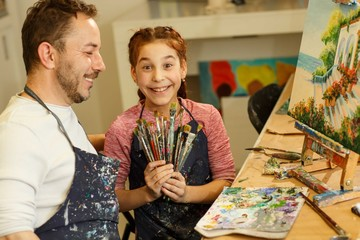 Positivity and creativity family holding, showing brush for drawing picture by oil smiling at camera. Handsome brunette father and daughter having fun, studying in school of arts.