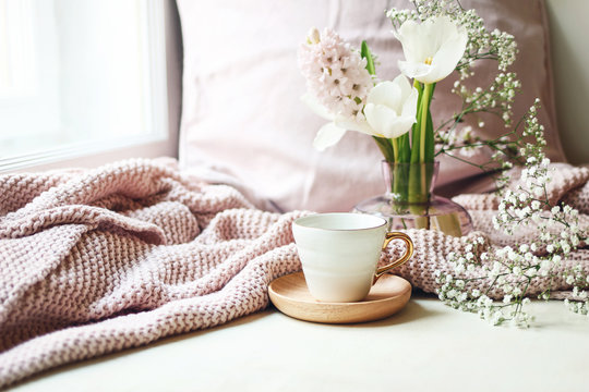 Cozy Easter, spring still life scene. Cup of coffee, pink knitted plaid and floral bouquet in vase on windowsill. Vintage feminine styled photo. Composition with tulips, hyacinth and Gypsophila