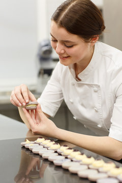 Cute and beautiful young girl wearing white uniform and working in confectionery. Female confectioner joining two parts of cookies and making macarons. Row of delicious macarons placed on table.