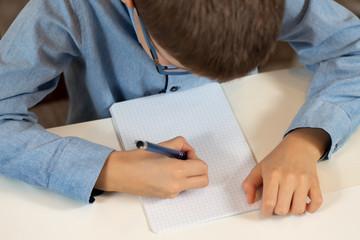 Obraz Chłopiec siedzi przy biurku z długopisem w dłoni i pisze w zeszycie. - fototapety do salonu