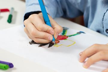Obraz Dłonie dziecka trzymają długopis i rysują wymyśloną postać na białej kartce papieru. - fototapety do salonu