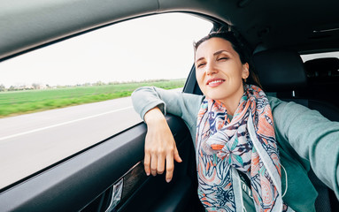 Woman in car portrait with wavy hair looks out car window wide angle shot.