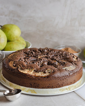 Homemade Chocolate Pear Cake.  Whole cake close up.  Ripened pears in the background.