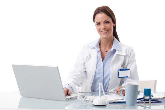 Happy doctor using laptop