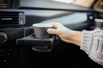 cup holder in the car. female hand with coffee on a trip.