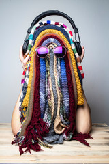 Young girl is fooling around in the winter while waiting for the summer and jokingly made a funny mask of multicolored scarves in the shape of rastaman face with dreadlocks, headphones and sunglasses.