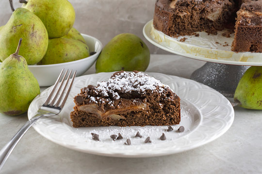 Side view of chocolate pear cake with fork, chocolate chips, and powdered sugar.  Pears and full cake in background.