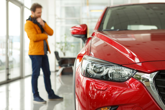 Front view of headlight of beautiful red automobile. Male customer choosing cars and thinking about features on background. Concept of car dealership, purchase and service.