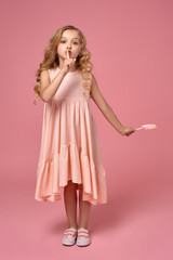 Little girl with a blond curly hair, in a pink dress is posing with a candy
