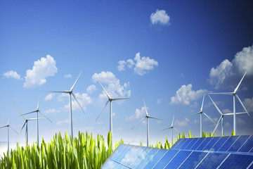 Sustainable natural energy concept with wing turbines and photovoltaic panel under blue sky