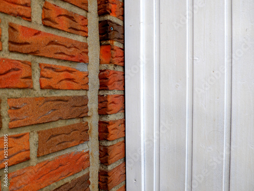 Wooden Weatherboard Painted White As A Background And Red Brick Wall