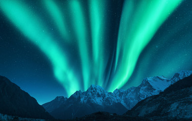 Aurora borealis above snow covered mountain range in europe. Northern lights in winter. Night landscape with green polar lights and snowy mountains. Starry sky with aurora. Nature background. Space