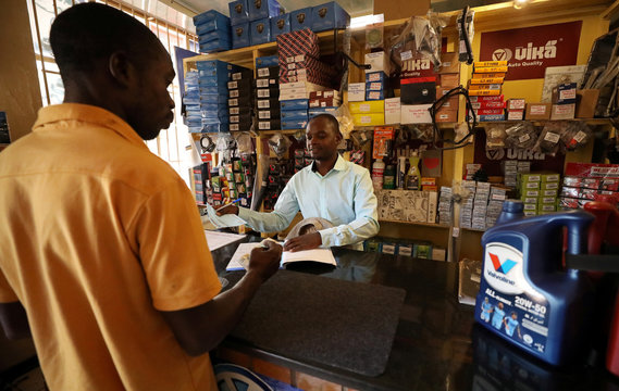 Godfrey Chinani deals with a customer buying car parts at his shop in downtown Harare