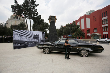 "A woman poses for a photo with one of the cars used in ""Roma"" movie during Roma Fest at Monumento a la Revolucion in Mexico City"