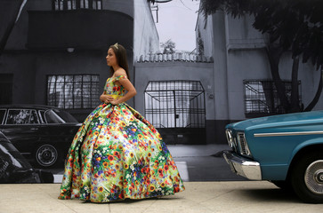 "A Quinceanera poses for a photo with one of the cars used in the ""Roma"" movie during Roma Fest at Monumento a la Revolucion in Mexico City"