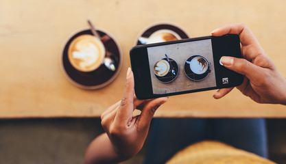 Woman photographing coffee with smart phone