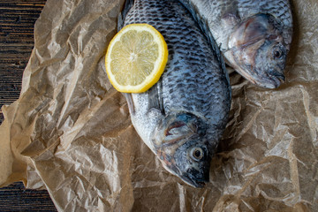Two whole Tilapia uncooked with lemons on wax paper and dark wood background flat lay