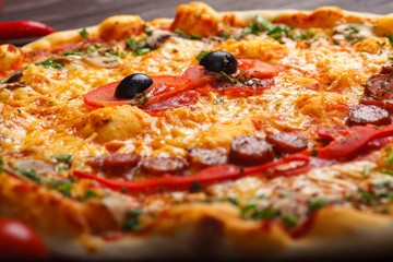 Close up top view smiling face Italian pizza for children with melted cheese, sausage snack sticks, salami, red tomatoes and fresh green herbs spices on a brown table