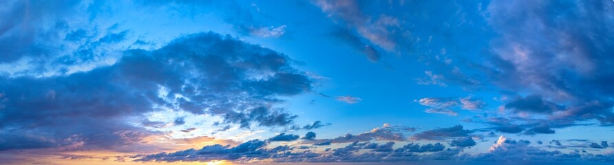 Twilight sunset. Panorama of cloudy sky with colorful clouds from blue to orange. High resolution panoramic sky