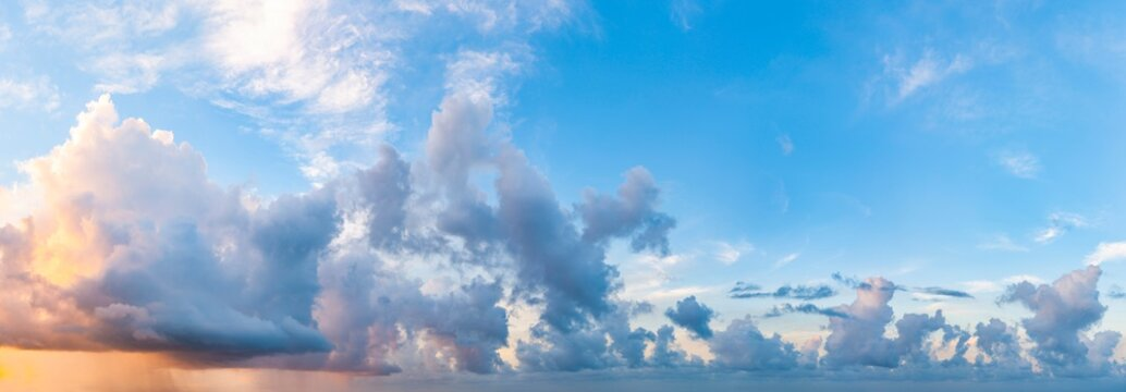 Twilight sunset. Panorama of cloudy sky with colorful clouds from blue to orange. High resolution panoramic sky. Cumulus formation.