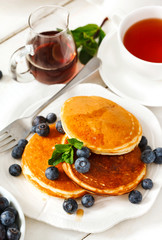 Pancakes with berries and maple syrup.