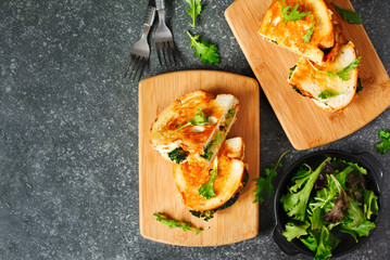 Broccoli and cheddar cheese sandwiches on wooden cutting boards, top view.