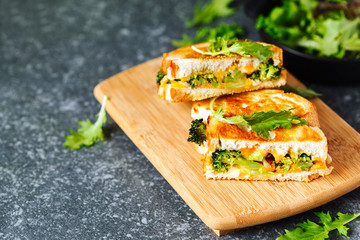 Broccoli and cheddar cheese sandwiches on wooden cutting boards.