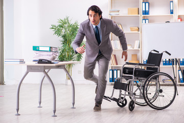 Young handsome employee in wheelchair at the office