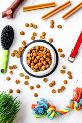 Pets accessories in home. Dog food in bowl, toys on white background top view