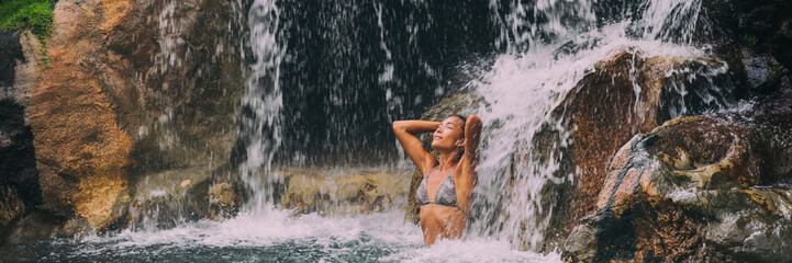 Wall Mural - Waterfall woman relaxing in spa resort pool banner. Panoramic crop, wellness relaxation health concept in nature tropical travel vacation background. Beautiful Asian bikini girl. Landscape horizontal.