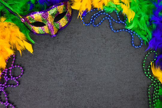 Festive Mardi Gras Carnival Mask and Feather Boa Over Blackboard Background with Copy Space