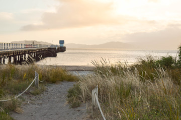 Small wooden shed and the end of a long straight pier over the shoreline in Wellington, New Zealand.