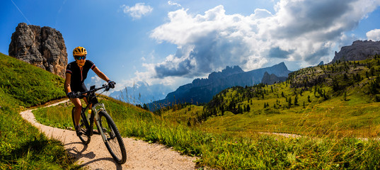 Wall Mural - Tourist cycling in Cortina d'Ampezzo, stunning Cinque Torri and Tofana in background. Man riding MTB enduro flow trail. South Tyrol province of Italy, Dolomites.
