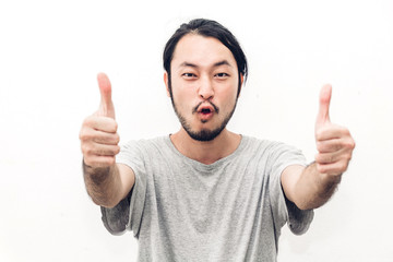 Portrait of happy smiling asian young handsome man with thumb up on white background