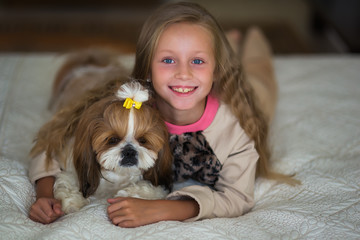 Cute girl with long hair is lying on the sofa with a dog at home.