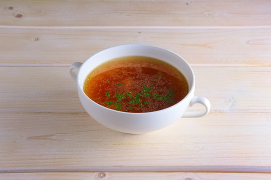 Rich beef broth in small soup bowl Served with fresh dill  on wooden table